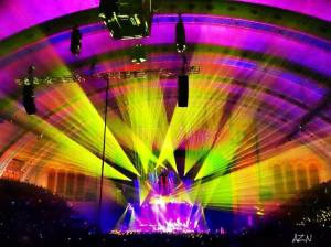 Distant shot of band on concert star with purple, green, and yellow lights at center