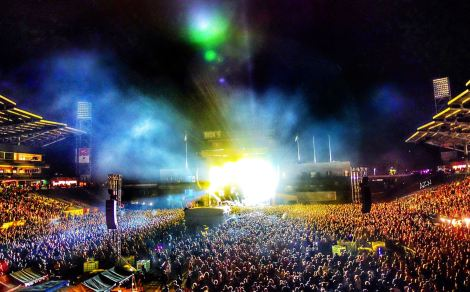 Picture of concert crowd with bright stage lights in center